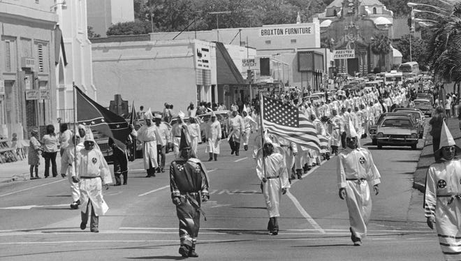 Members of the Ku Klux Klan stage a march prior to their cross burning ceremony on Saturday, May 24, 1975, in Pensacola. The group, numbering about 135, staged the silent, peaceful march on May 24, 1975, in an effort to bring townspeople to the meeting later at night.