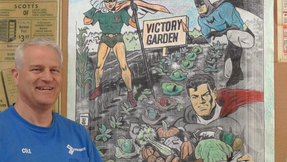 Cole Kleitsch stands next to a victory garden poster