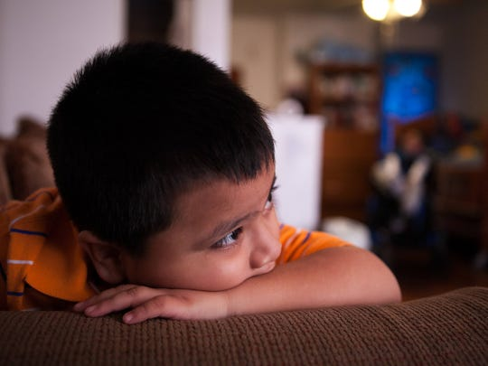 Joel Zaveleta sits in the living as his mother Luz Moyao and brother, Angel Zaveleta, relax at home in Wilmington.