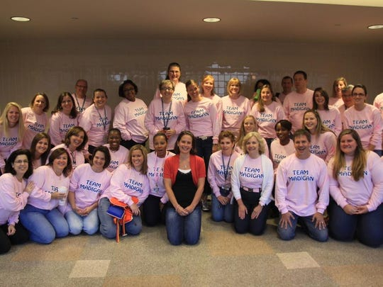 """Teachers at Kennett Middle School rallied around breast cancer survivor and eighth grade teacher Kate Madigan on her last day of work before surgery in 2012. They all are wearing """"Team Madigan"""" shirts."""