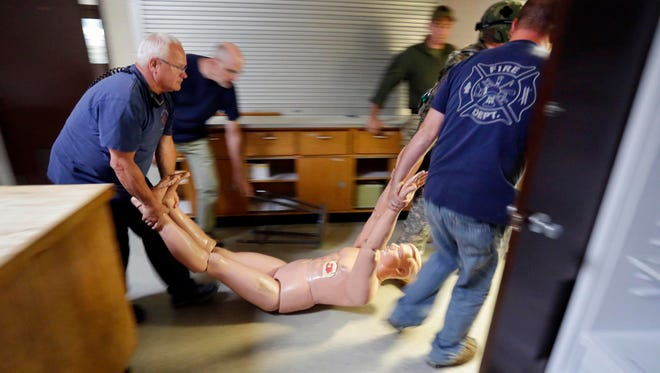 EMTs carry out a shooting 'victim' during a training session held by the Reserve Task Force Tuesday, Sept. 8, 2015, at the old Willigen school near Haven.