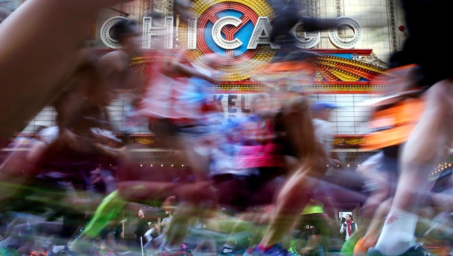 Runners pass the Chicago Theatre on State Street during last year's Chicago Marathon.