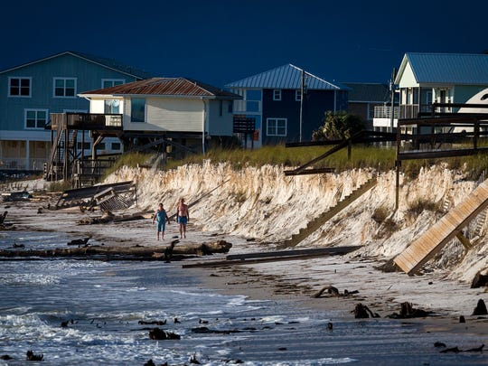 Beachgoers survey the erosion damage caused by a strong storm in Cape San Blas, Fla. in October 2015. Property owners and local officials have struggled to address the critical erosion issues facing the Panhandle beach destination.