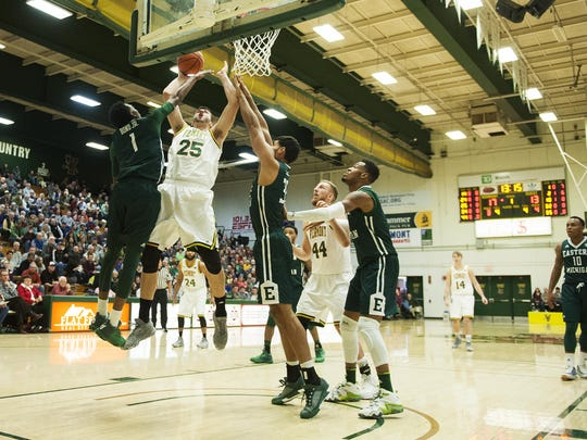 Vermont's Drew Urquhart (25) leaps over Eastern Michigan's Tim Bond (1) for a lay up during the men's basketball game between the Eastern Michigan Eagles and the Vermont Catamounts at Patrick Gym on Saturday afternoon December 17, 2016 in Burlington.