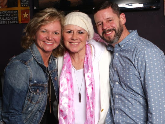Anita Cochran (center) was surprised at her benefit concert by longtime South Lyon friends Jodi Bomay West (left) and Brian Doyle.