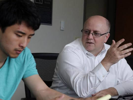 Wisconsin Institute for Public Policy and Service Director Eric Giordano, right, discusses operations with Tim Yuan at the organization's office in June 2014 at the University of Wisconsin Marathon County in Wausau.