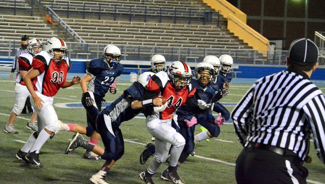 The Trojans' Ty Molina (44) fights for extra yards against the Falcons in Elks Little Cavemen Super Bowl XVII Friday at Ralph Bowyer Stadium. The Falcons won in overtime, 22-20. Visit currentargus.com to see more photos from Friday's game.