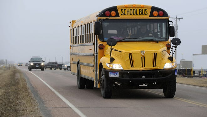 A Lennox school bus drives by the industrial park around 4:30 where shootings took place in Lennox on Thursday.