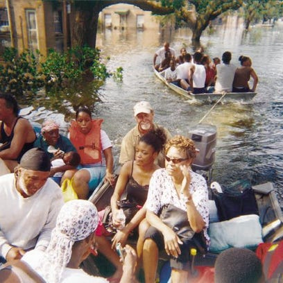 Dennis Talbot of Lafayette (with goatee and white cap) ferries Hurricane Katrina victims toward dry land in east New Orleans.