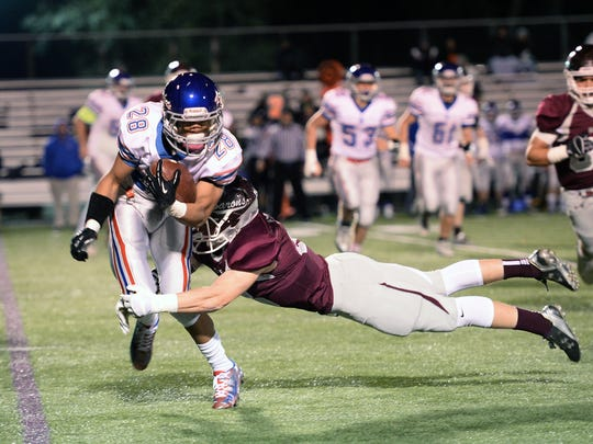 Spring Grove's LJ Chisholm is wrapped up  by Manheim Central's Drew Eshleman in the opening round of the District 3 Class AAA playoffs. The Barons won, 51-3.