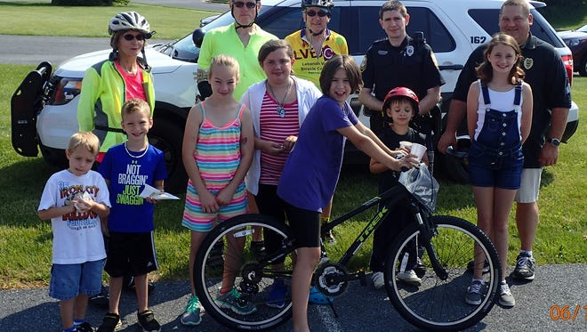 Ten children participated in the Cleona Police Department bicycle rodeo held earlier this month at the police station, 140 W. Walnut St., Cleona. Pictured with children at the event, are, back row, from left, Pat and Ed Krebs and Mike Sheehan, all of the Lebanon Valley Bicycle Coalition; and Officer Robert Henning Jr. and Sgt. Matthew Rager, both of the police department. The rodeo was open to children 12 and under who reside in the Annville-Cleona School District. The members of the Bicycle Coalition stopped by to show their support.