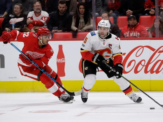 Calgary Flames defenseman Mark Giordano (5) controls the puck as Detroit Red Wings left wing Andreas Athanasiou (72) closes in during the second period of an NHL hockey game, Wednesday, Nov. 15, 2017, in Detroit. (AP Photo/Carlos Osorio)