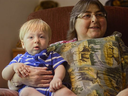 Tammy Shackett holds her one-year-old grandson Killian, a pillow on her chest to protect the an incision made during her double-lung transplant surgery.