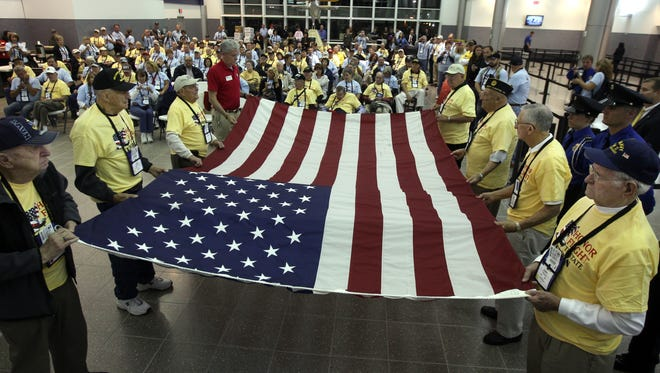 World War II and Korean veterans prepare to fold a flag at the airport before boarding an Honor Flight.