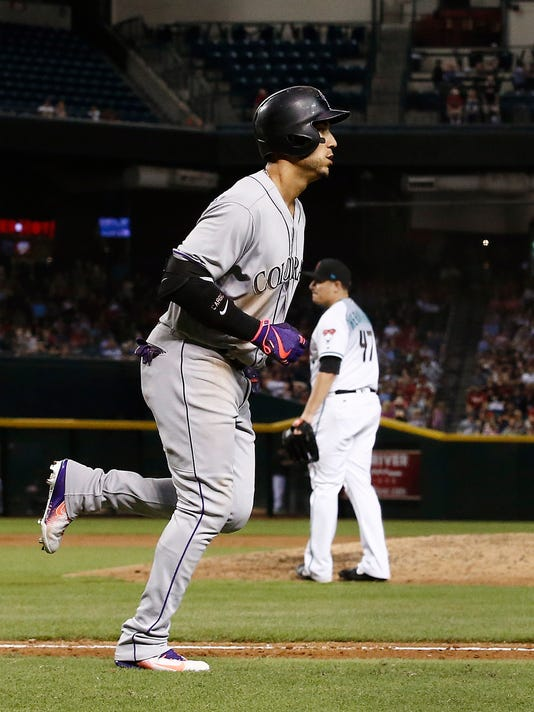Colorado Rockies' Carlos Gonzalez, left, rounds the bases after hitting a two-run home run off Arizona Diamondbacks' David Hernandez (47) during the seventh inning of a baseball game Tuesday, Sept. 12, 2017, in Phoenix. (AP Photo/Ross D. Franklin)