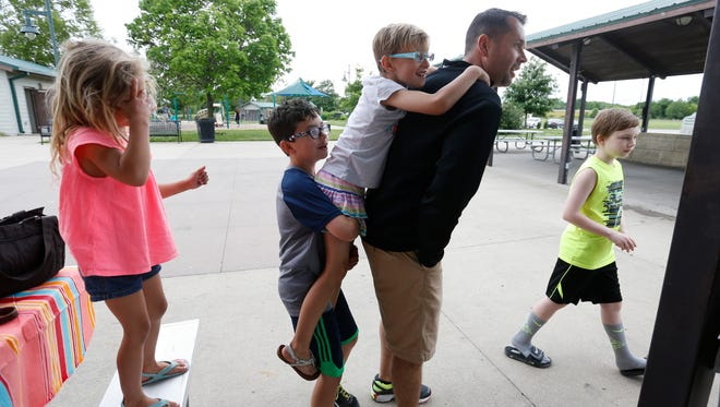 Myra, 5, looks on as her brothers Brendan, 10, and Ryland, 9, jump on their father, Brian Kelting, on Saturday, May 28, 2016, during a gathering of the Little Rainbows support group at Raccoon River Park in West Des Moines.