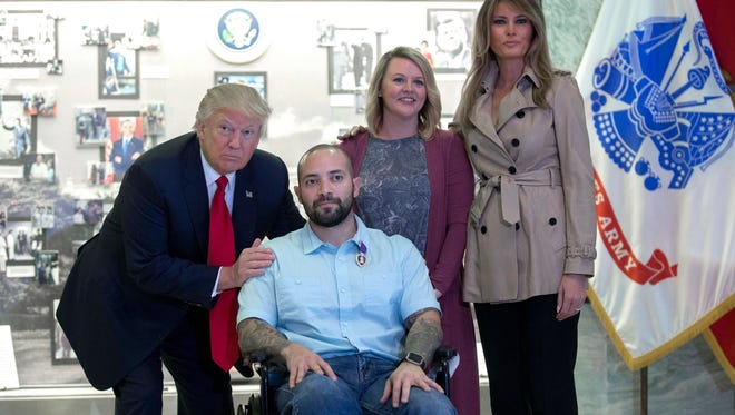 President Trump and first lady Melania Trump talks with Sergeant First Class Alvaro Barrientos and his wife Tammy after awarding the Purple Heart to him during a visit to Walter Reed National Military Medical Center in Bethesda, Maryland Saturday.