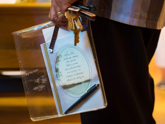 Family member Patricio Agas holds a card that reads,