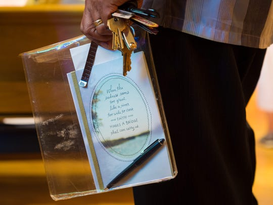 "Family member Patricio Agas holds a card that reads, ""When the sadness seems too great, like a river too wide to cross, faith makes a bridge that can carry us,"" as he arrives for the nine-day novena (prayer) ceremony Tuesday night to remember the Trinidad family. Audie Trinidad, who was an usher at Saint Anastasia Catholic Church, always saved a spot for his family during Sunday services."