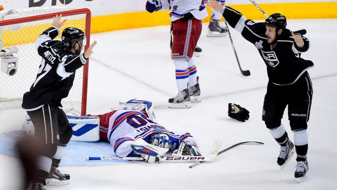 Kings defenseman Alec Martinez (left) celebrates after scoring the winning goal with Kyle Clifford (right) past Rangers goalie Henrik Lundqvist during the second overtime period in Game 5.