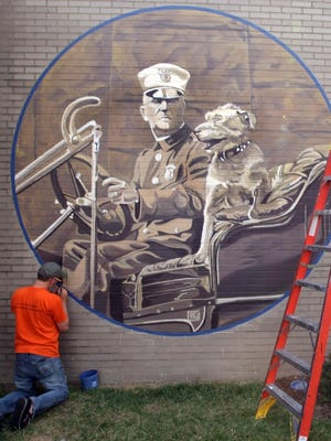 Cincinnati artist Michael Stillion creates a mural in 2008 of Cincinnati's first police dog and his handler on one of the wall of The Greater Cincinnati Police Museum.