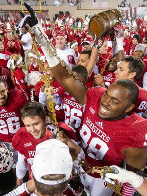Indiana's Adarius Rayner (99) celebrates with the Old Oaken Bucket trophy, Nov. 30, 2013.