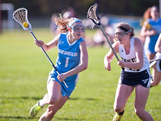 South Burlington's Willow Yager, left, looks to beat an Essex defender during Tuesday's high school girls lacrosse game in Essex.