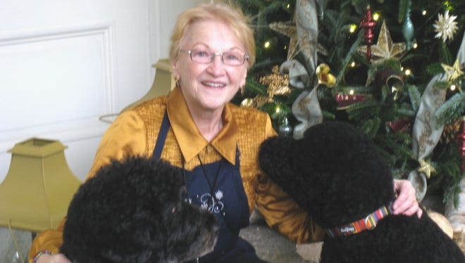 Surprise resident Nan Adams, who volunteered to help decorate the White House for the holidays, poses with the Obama dogs, Bo and Sunny in the East Wing.
