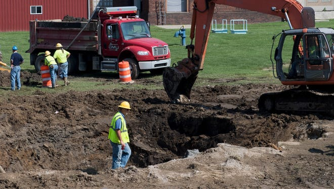 An Owensboro Municipal Utility worker on Tuesday walks along the top of a pit on Fourth Street that was dug up after two water mains broke in Owensboro, Kentucky on Monday.
