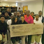 Opelousas Mayor Reggie Tatum visits the Opelousas High School band room and presents a personal check in the amount of $1000 to help defray cost of the band's trip to the Memorial Day Parade in Washington D.C.