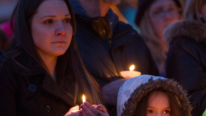 Christina Cantu and her daughter Breyana Cantu listen as Bravo Squad Sgt. Clint Hill describes fallen officer Tyler Stewart during a candlelight vigil at the Flagstaff Police Department a day after he was shot and killed in Flagstaff on Dec. 28, 2014.