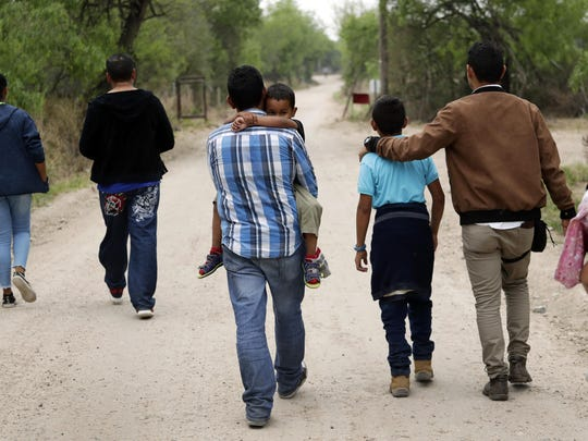 In this March 14, 2019, file photo, a group of migrant families walk from the Rio Grande, the river separating the U.S. and Mexico in Texas, near McAllen, Texas, right before being apprehended by Border Patrol.