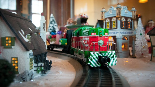 A Christmas-themed O Gauge Lionel Train bearing miniature presents goes around a 6-foot by 6-foot illuminated model village at the Las Cruces Railroad Museum. The village, built by Tom and Karen O'Brien, will be running from 6 to 9 p.m., seven days a week, throughout the holiday season.