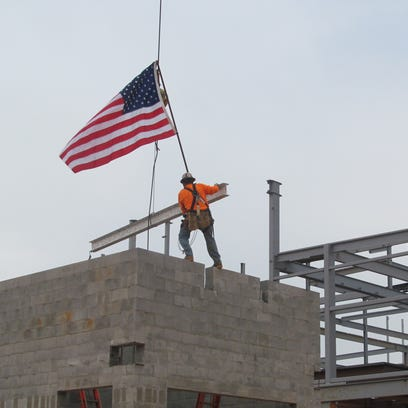Workers position the final beam signed by military