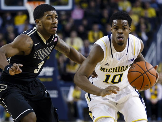 Jan 30, 2014; Ann Arbor, MI, USA; Michigan Wolverines guard Derrick Walton Jr. (10) moves the ball defended by Purdue Boilermakers guard Ronnie Johnson (3) in the first half at Crisler Arena. Mandatory Credit: Rick Osentoski-USA TODAY Sports