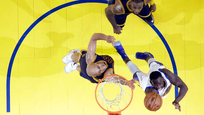 Golden State Warriors' Draymond Green, bottom, right, shoots past Cleveland Cavaliers' LeBron James, top, and Richard Jefferson during the second half in Game 2 of basketball's NBA Finals Sunday in Oakland, Calif.