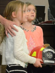 Zara, 4, and Zurie, 5, Williamson wait to present a new helmet to their father, Lt. Scott Williamson, at the Battle Creek Fire Department promotion ceremony Tuesday.