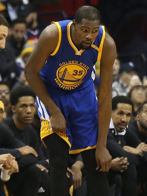 Golden State Warriors forward Kevin Durant (35) holds his left knee after being inured against the Washington Wizards in the first quarter at Verizon Center.