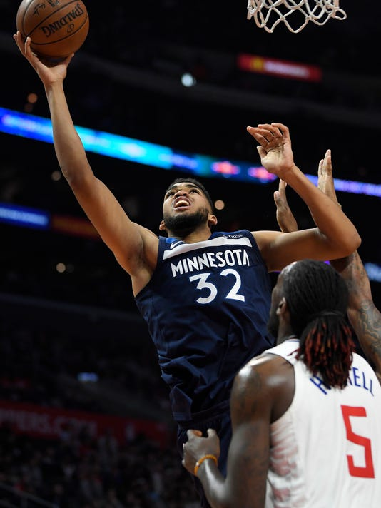 Minnesota Timberwolves center Karl-Anthony Towns, left, shoots as Los Angeles Clippers forward Montrezl Harrell defends during the second half of an NBA basketball game, Monday, Jan. 22, 2018, in Los Angeles. The Timberwolves won 126-118. (AP Photo/Mark J. Terrill)