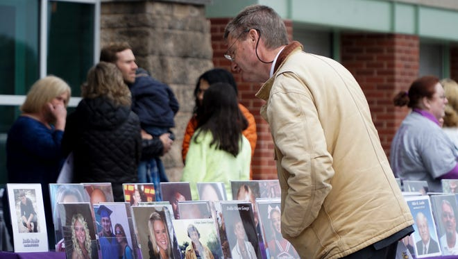 Former Knox County Mayor Tim Burchett examines a row of pictures of victims of violent crime during a ceremony on April 8, 2018. (News Sentinel file photo)