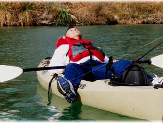 Heroes on the Water relaxing on top of his kayak.