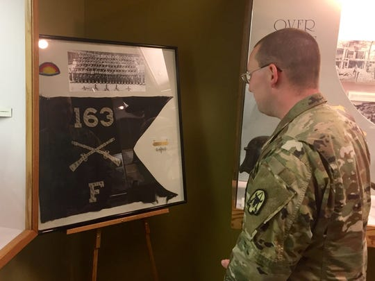 Capt. Ryan Finnegan looks over a display honoring the 163rd Infantry Regiment at the Montana Military Museum.