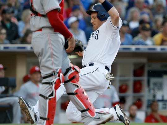 San Diego Padres' A.J. Ellis, right, scores on a sacrifice fly by Eric Lauer during the second inning of a baseball game against the Cincinnati Reds in San Diego, Saturday, June 2, 2018. (AP Photo/Alex Gallardo)