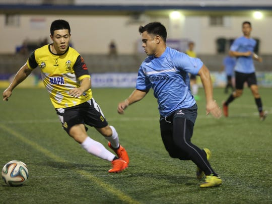 : Sidekicks' Anthony Villena attempts to get past NAPA Rovers' Min Sung Choi during a Week 5 match of the Budweiser Soccer League Saturday night at the Guam Football Association National Training Center. The Rovers won 4-0.