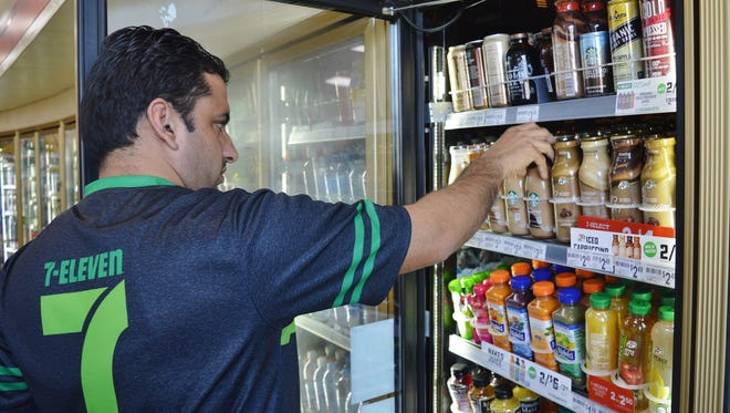 Sammy Dhaliwal straightens the ready-to-drink cold brews at 7-Eleven in Visalia.