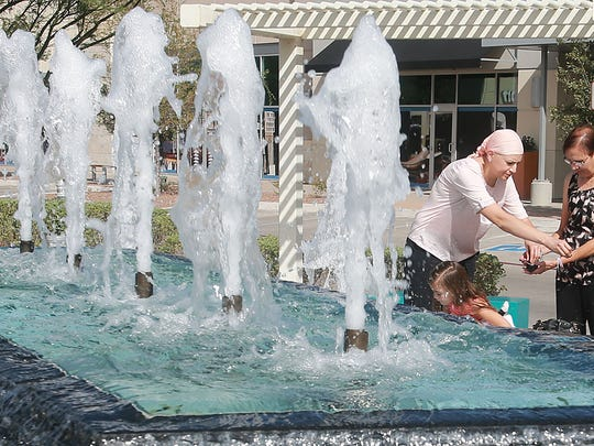 Kristol Veach took coins offered to her by her mother, Mother Reyes, to give to daughters Ava Reyes and Aubrey Reyes to throw into a fountain at The Fountains at Farah Monday.