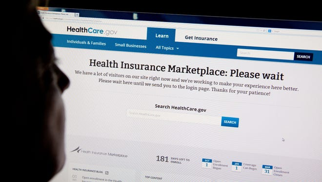 "A woman looks at the HealthCare.gov insurance exchange website showing a ""Please wait"" page, in this Oct. 1, 2013, file photo in Washington, D.C."
