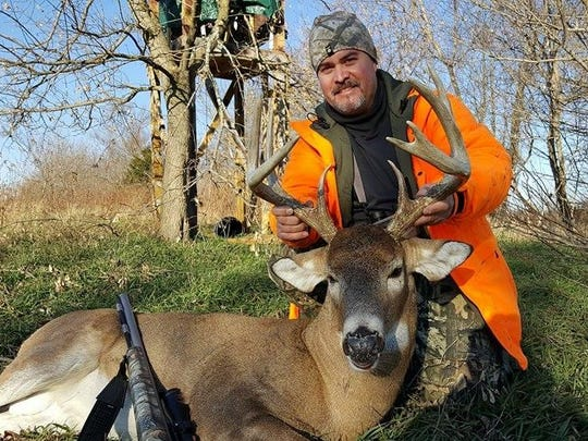 A hunter poses with a whitetail deer.