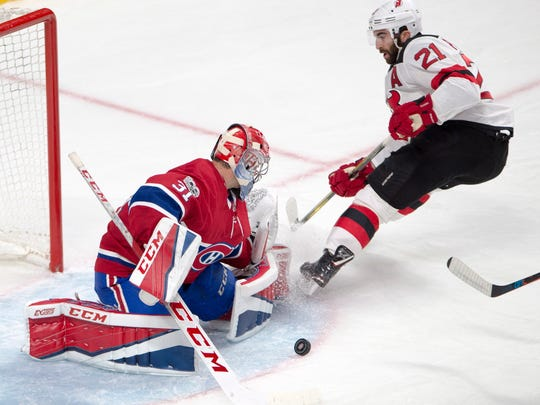New Jersey Devils right wing Kyle Palmieri (21) is stopped by Montreal Canadiens goalie Carey Price (31) during the second period of a preseason NHL hockey game, Thursday, Sept. 21, 2017 in Montreal. (Ryan Remiorz/The Canadian Press via AP)