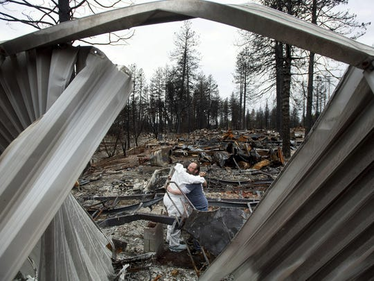 In this Feb. 8, 2019, photo, Bud Daneau hugs Carol Beall while helping her comb through her residence, destroyed by the Camp Fire, at the Ridgewood Mobile Home Park in Paradise, Calif.